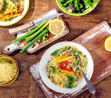 Couscous with vegetables on a wooden background. Flat lay