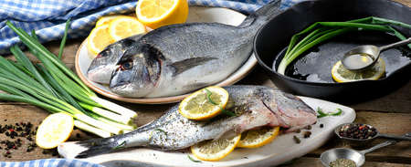 dorado fish: Raw fresh dorado fish on a wooden background. Top view. Stock Photo