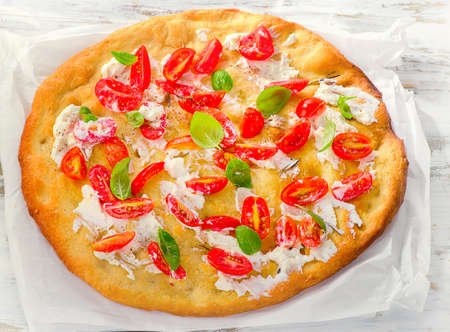 focaccia: Focaccia with tomatoes, cream cheese and basil. Top view