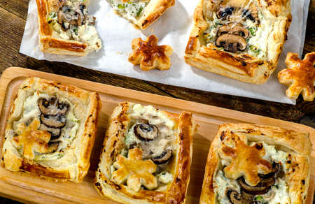 Puff pastry Mushroom tarts on a wooden board. top view