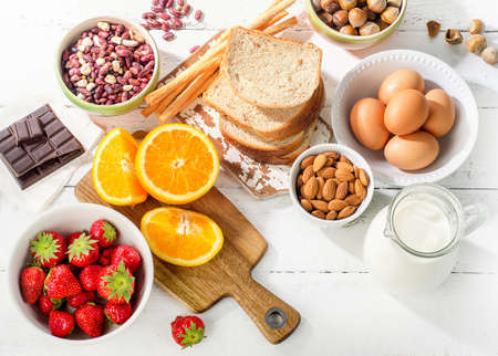 alergenos: Alergia concepto de alimentos. alergia alimentaria en el fondo de madera blanca. Vista superior Foto de archivo