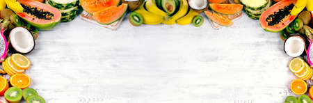 Exotic tropical fruits mix on white wooden background. Healthy eating concept.
