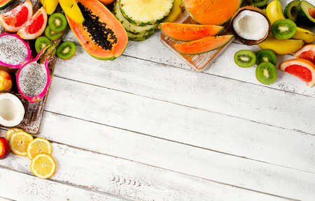 Exotic tropical fruits mix on a white wooden background. Healthy eating concept. Standard-Bild