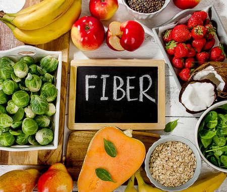Aliments riches en fibres sur un fond en bois blanc. Plat poser