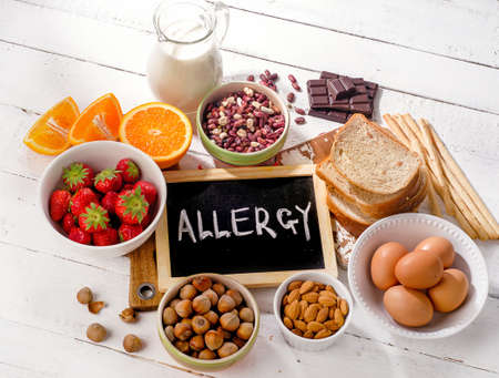 food allergy: Food allergy. Allergic food on  wooden background. View from above Stock Photo
