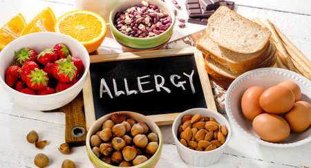 Food allergy. Allergic food on  white wooden background. Archivio Fotografico