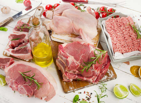 Different types of raw meat with fresh vegetables and spices.  View from above Фото со стока