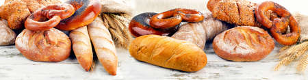 Assortment of  fresh baked bread on a wooden table isolated on a white background Stock Photo