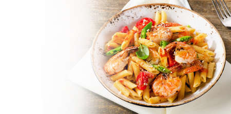 Penne pasta with shrimp, tomatoes and herbs on wooden background. Top view.