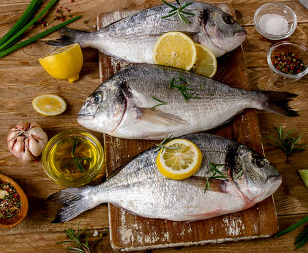 Fresh fishes with spices  on a wooden background. Healthy food concept.