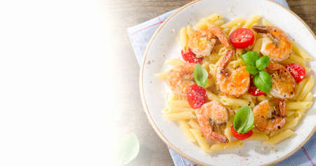 Penne pasta with shrimps, tomatoes and herbs. Top view