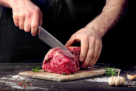 Man cutting raw beef meat. Stock Photo