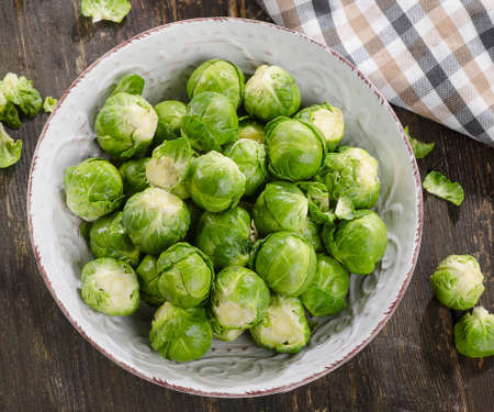 Brussel sprouts over rustic wooden table. Top view.