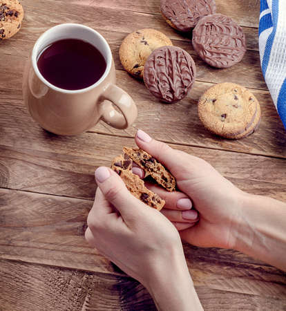 Woman hands with Cup of tea and cookies on wooden table. Top view Stock Photo