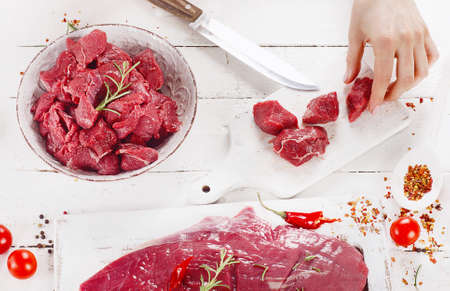 Woman hands cutting beef meat on a wooden background. Top view