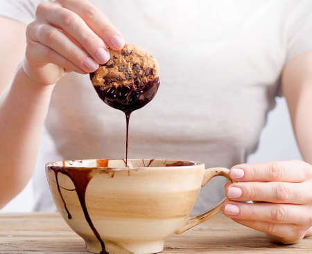 Woman hand dipping cookie in a  melted dark  chocolate. Selective focus