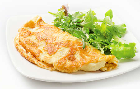 Omelette with fresh salad on white plate.