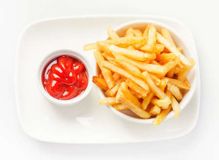 French fries served with tomato sauce on white plate. Top view