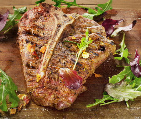 T-Bone Steak with Fresh Herbs on  a rustic wooden table Stock Photo