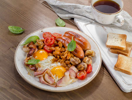 bacon baked beans: Full english breakfast with fried egg, beans, tomatoes, mushrooms, bacon, sausage and toasts Stock Photo