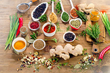 Various spices and herbs on rustic wooden background. Top view