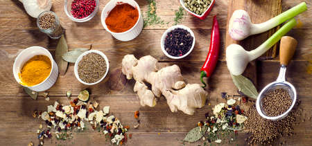 Colorful spices and fresh herbs on wooden table. View from above. Banner Stock Photo