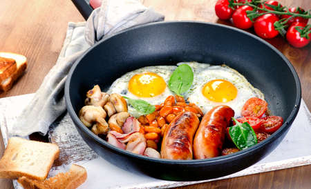 Full English breakfast with fried eggs, sausages, bacon, beans, toasts, tomatoes  and mushrooms.