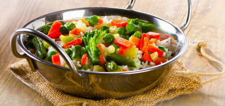 Rice with vegetables on a wooden background. Selective focus. Stock Photo