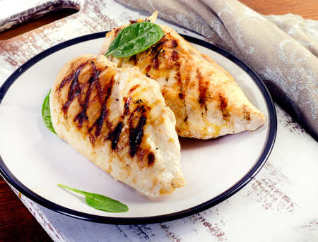 Grilled healthy chicken breasts on wooden table. Archivio Fotografico