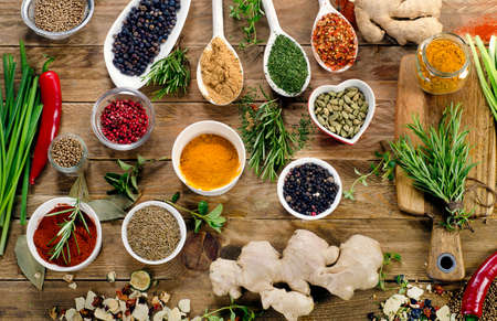 Various spices and fresh herbs on a rustic wooden background. Flat lay