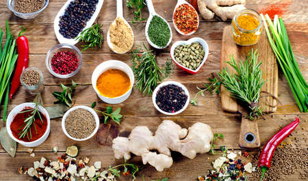 Various spices and fresh herbs on a rustic wooden background. Top view Stock Photo