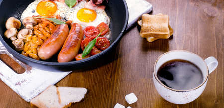 bacon baked beans: Full English breakfast with fried eggs, sausages, bacon, beans, toasts and coffee cup. Panorama
