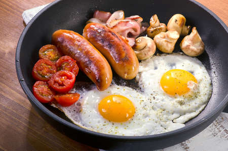 English breakfast in pan with fried eggs, sausages, bacon, beans, toasts and mushrooms