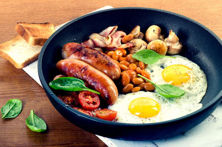bacon baked beans: English breakfast in pan with fried eggs, sausages, bacon, beans, toasts  and mushrooms.