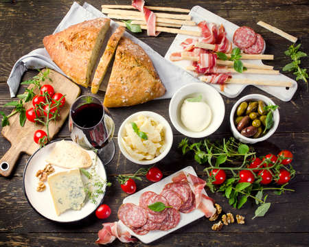 Different meat and cheese products with red wine on wooden table. View from above