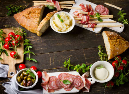 hams: Different meat and cheese products on a wooden board. Antipasti. Top view