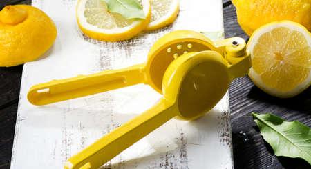 Lemon Squeezer en verse citroenen op een houten bord Stockfoto