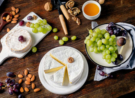Cheeses with grapes and almond on dark wooden board.
