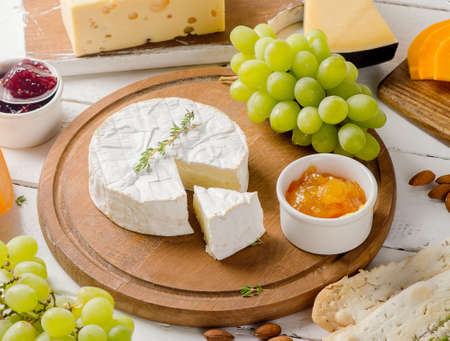 Different kinds of cheeses with grapes and jam on a wooden table.