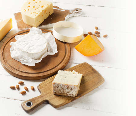 Cheese on  white wooden table.  Flat lay