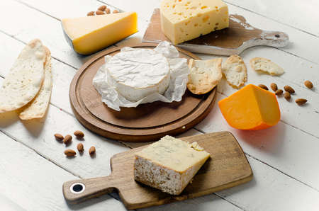 Cheese with almonds on a wooden board. Top view