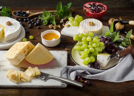 Cheese with grapes, honey and nuts  on  dark wooden table. Stock Photo
