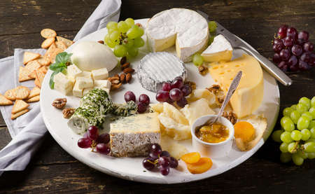 Cheese plates served with grapes, jam,  and nuts on a wooden board.Top view