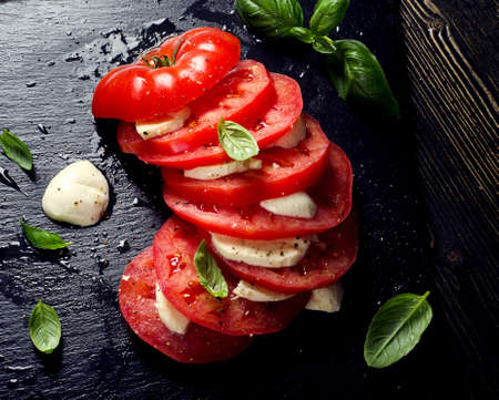 Tomatoes and mozzarella with basil. Healthy eating. Top view Stock Photo