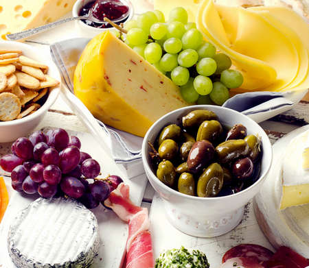 charcutería: Charcuterie assortment, cheeses, olives and fruits   on a white wooden background. Foto de archivo