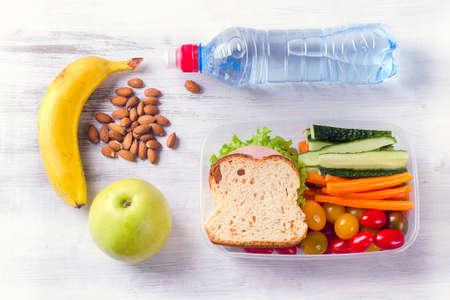 サンドイッチと新鮮な野菜、水のボトルと健康ランチボックス。健康的な食事の概念。上面図