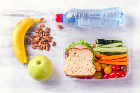 Healthy lunch box with sandwich and fresh vegetables, bottle of water. Healthy eating concept. Top view Stockfoto