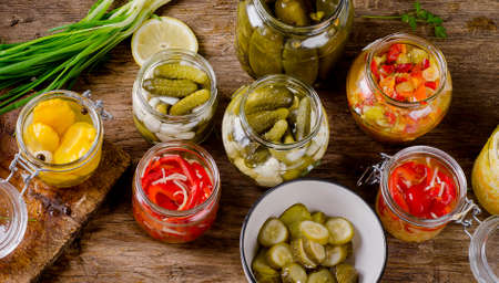 Fermented preserved vegetables on a dark rustic table. Stock Photo