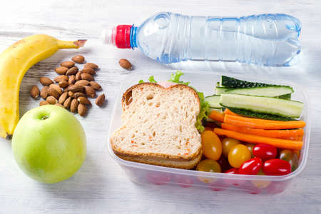 Healthy lunch box with sandwich and fresh vegetables, bottle of water. Healthy eating concept. Top view Фото со стока