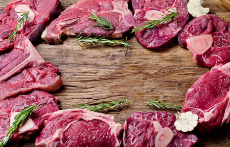 Raw meat on a dark wooden board. Food high in protein Stock Photo